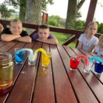 2021-07 - Spotkanie w Macierzyszu - kolory. Zdjęcie ukazuje dzieci oglądające jak kolorowa woda przepływa między szklankami zmieniając jednocześnie barwę.