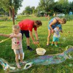 2021-07 - Spotkanie w Macierzyszu - kolory. Zdjęcie ukazuje puszczanie wielkich baniek mydlanych. Na pierwszym planie dziewczynka puszczające ogromną bańkę.